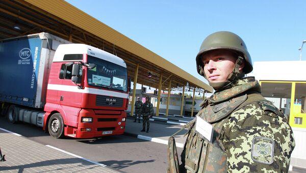 Украинский пограничник стоит у грузовика с гуманитарной помощью из Германии на пограничном пункте в западной Украине. 7 октября 2014