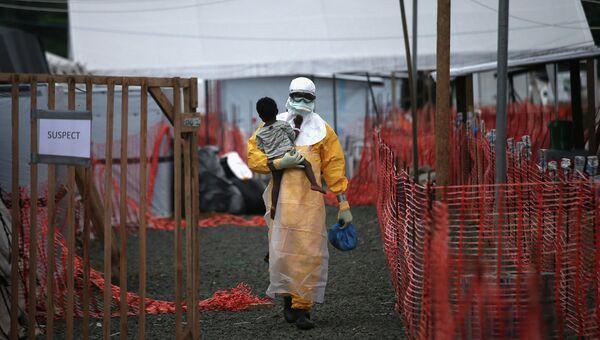Доктор из организации Врачи без границ несет на руках ребенка с подозрением на вирус Эбола