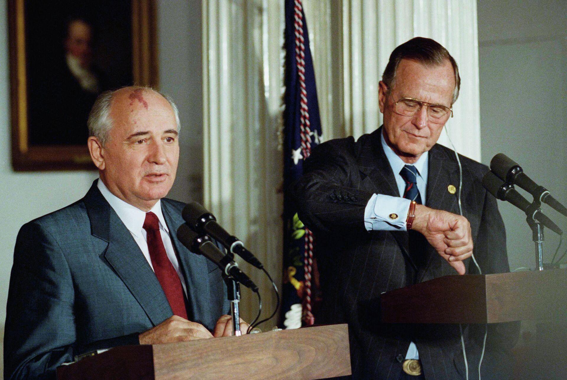 Президент США Джордж Буш смотрит на часы во время совместной пресс-конференции с президентом СССР Михаилом Горбачевым в Лондоне, 1991 год - РИА Новости, 1920, 03.12.2020