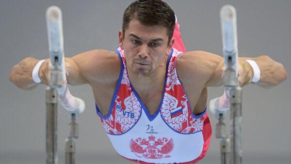 Николай Куксенков (Россия) выполняет упражнения на брусьях. Архивное фото