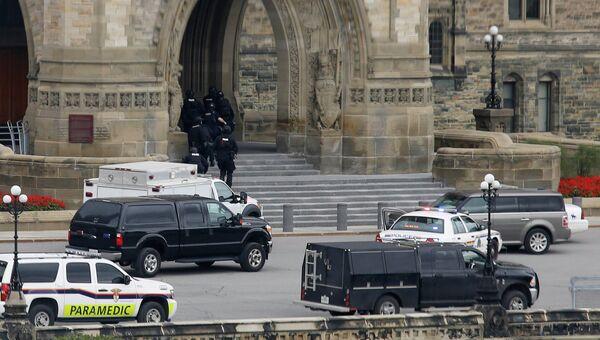 Полицейски входят в здание парламента Канады в Оттаве 22 октября 2014