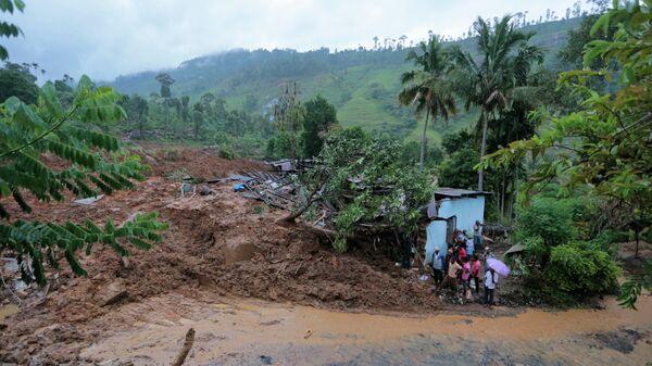 Жители стоят у разрушенного оползнем дома, округ Бадулла, Шри-Ланка