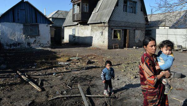Женщина с детьми у своего дома, пострадавшего в результате артиллерийского обстрела украинскими силовиками города Донецка. Архивное фото