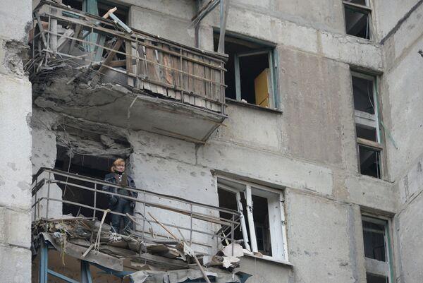 Женщина на балконе дома подвергшегося обстрелу украинскими военными