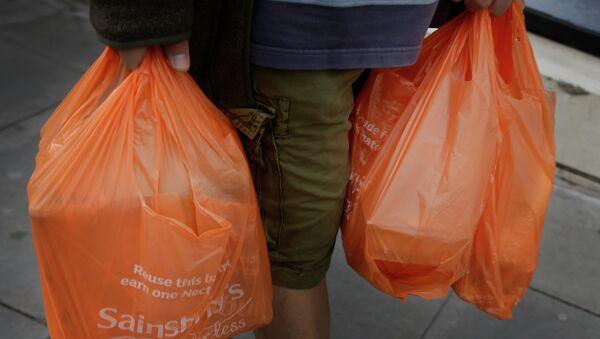Человек с пакетами, заполненными продуктами в Лондоне. Архивное фото