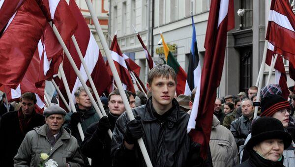Люди несут флаги памятнику Свободы в честь солдат Латышского добровольческого легиона СС. Рига, Латвия. Архивное фото