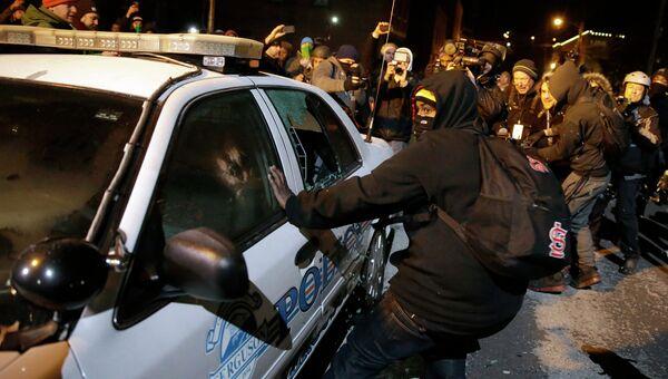 Протестующие разбивают полицейский автомобиль в Фергюсоне. 25 ноября 2014