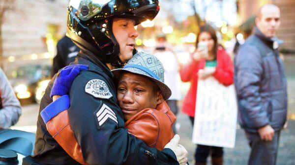 Сержант полиции обномает мальчика на митинге в Портленде