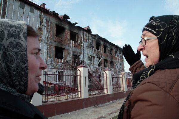 Женщины у поврежденной школы №20 в центре Грозного