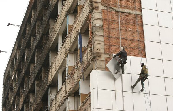 Рабочие снимают для ремонта обшивку с Дома Печати в центре города Грозного