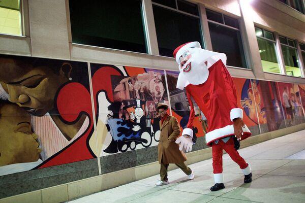 Человек в костюме гигантского Санта-Клауса возвращается домой после церемония украшения елки в штате Пенсильвания