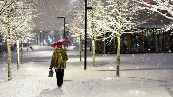 Женщина с зонтом идет по парку Музеон во время снегопада в Москве