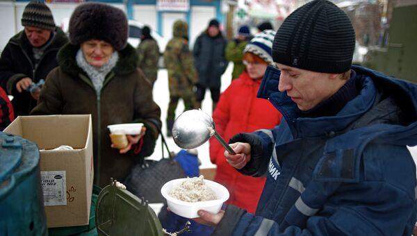 Работник аварийно-спасательной службы раздает еду на востоке Украины. Архивное фото