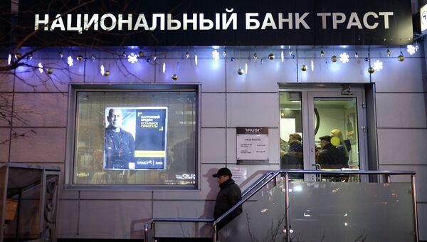 Клиент выходит из офиса банка Траст в Москве