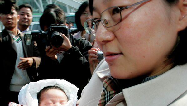 Жительница Южной Кореи Хван Сон с ребенком. Архивное фото