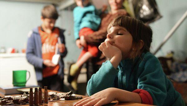 Девочка играет автоматными гильзами в подвале 21-й городской больницы, где она живет с родителями