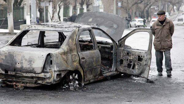 Сгоревший автомобиль недалеко от обстрелянной остановки транспорта в Донецке