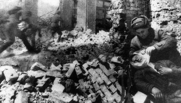 Медсестра перевязывает раненого солдата во время уличных боев в Сталинграде