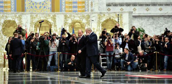 Президент России Владимир Путин и президент Белоруссии Александр Лукашенко проходят мимо журналистов во Дворце независимости в Минске