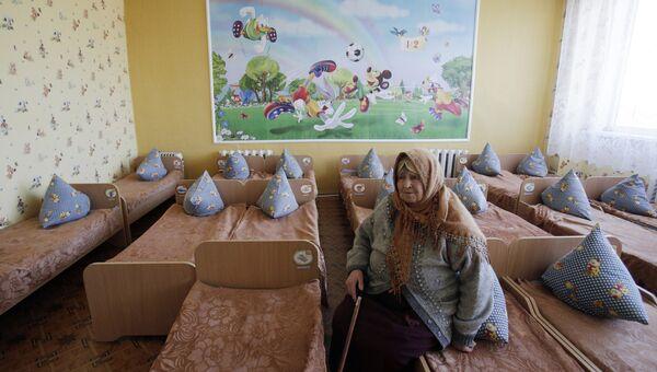 Пожилая женщина сидит на кровати в детском саду. Архивное фото