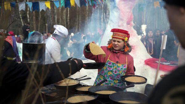 Девочка жарит блины во время празднования масленицы в деревне Хлюпино