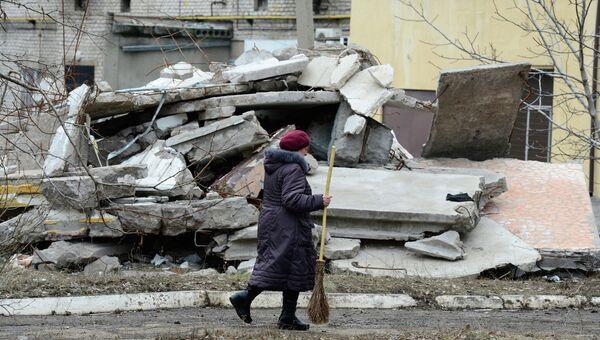 Женщина идет мимо разрушенного дома в Первомайске, Архивное фото