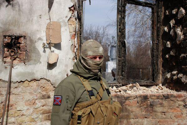 Ополченец ДНР у разрушенного здания в Донецке