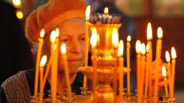 Прихожанка во время богослужения в праздник Входа Господня в Иерусалим в грозненском храме Михаила Архангела
