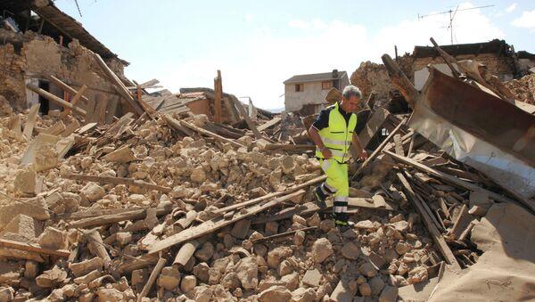 Спасатель на месте разрушенного в результате землетрясения дома в Аквиле, Италия. Архивное фото