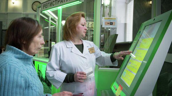 Сотрудница городской поликлиники помогает пациентке оформить талон на прием к врачу в терминале электронной очереди. Архивное фото