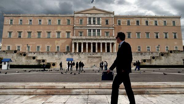 Мужчина проходит возле здания парламента Греции в Афинах. Архивное фото