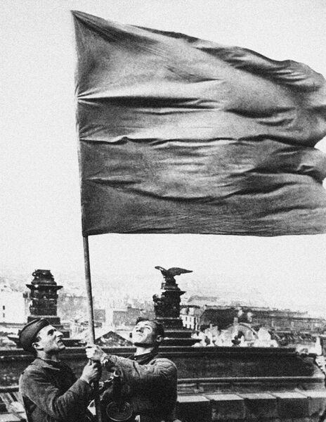 Два бойца держат развевающееся знамя стоя на крыше рейхстага