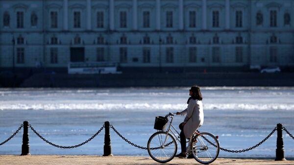 Девушка едет на велосипеде по Набережной Невы в Санкт-Петербурге