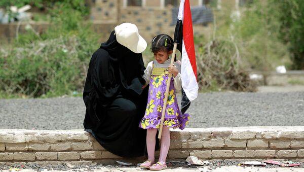 Женщина и ребенок с флагом Йемена во время митинга в Сане. Архивное фото