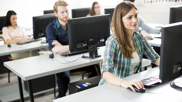 Молодые люди за компьютерами. Архивное фото