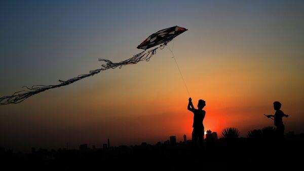 Дети запускают воздушного змея в парке Каира, Египет. Июнь 2015