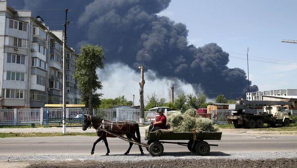 Житель проезжает мимо горящего нефтехранилищя в Киевской области, Украина. Июнь 2015