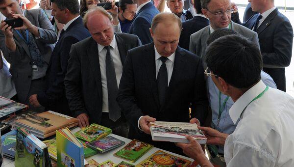 Президент России Владимир Путин (в центре) и советник президента РФ по культуре Владимир Толстой во время посещения открывшийся на Красной площади Московский фестиваль Книги России