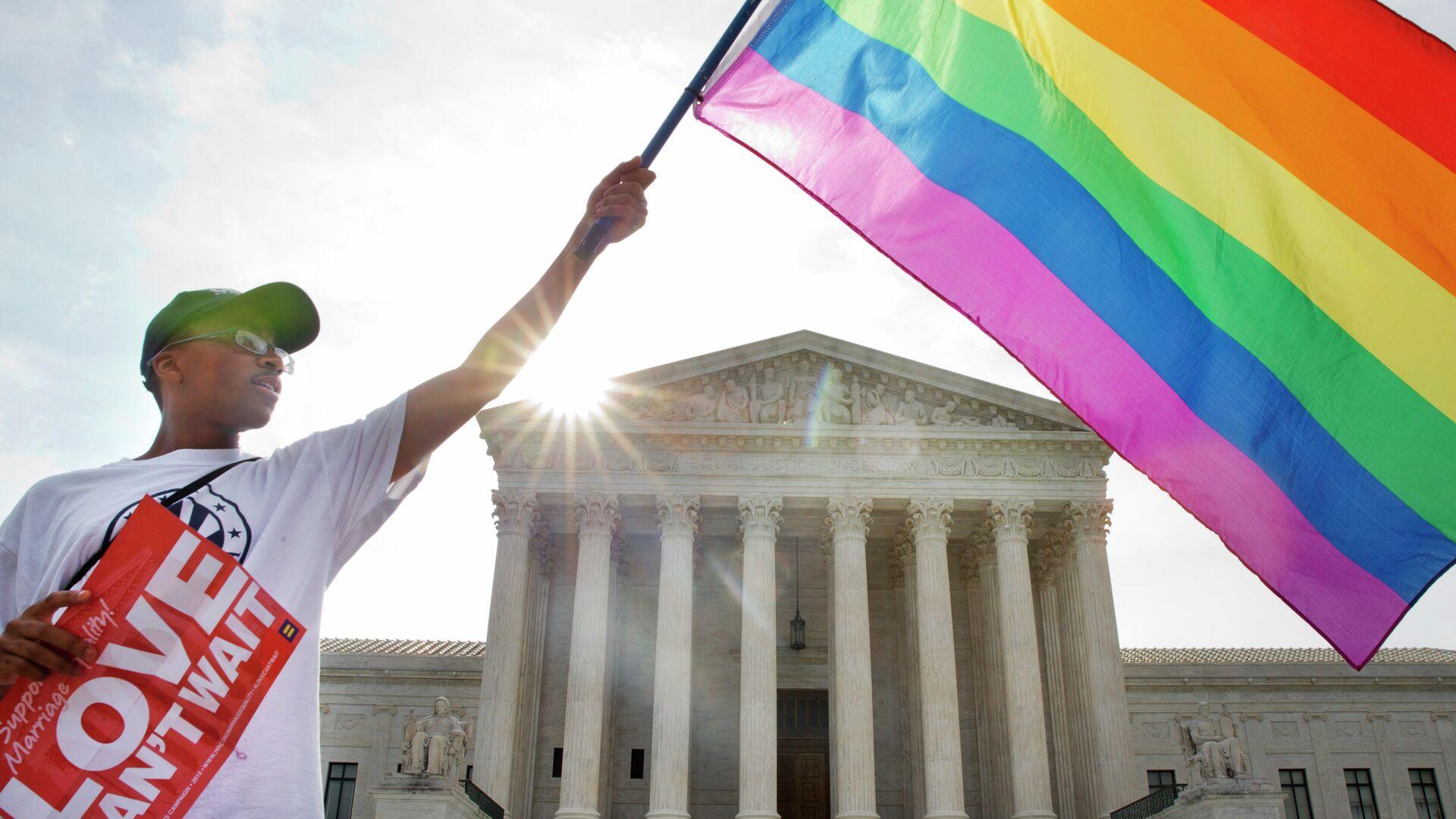 Активист держит флаг ЛГБТ у здания Верховного суда США в Вашингтоне - РИА Новости, 1920, 01.11.2020