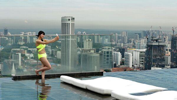 Посетительница бассейна на крыше небоскреба в Сингапуре. 2014 год