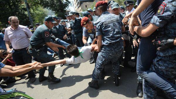 Сотрудники полиции задерживают участника акции протеста против повышения тарифов на электроэнергию в Ереване