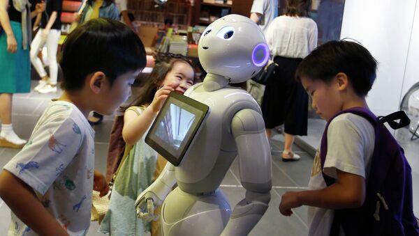 Дети окружили робота Pepper в магазине Токио, Япония. Июль 2015
