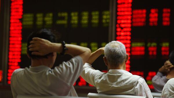 Инвесторы следят за котировками фондового рынка Китая в Пекине