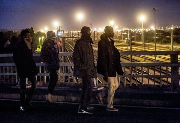 Мигранты пересекают мост над железнодорожными путями Евротуннеля в городе Кале