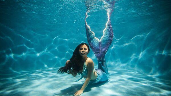 Девушка в костюме русалки в бассейне города Чунцин, Китай