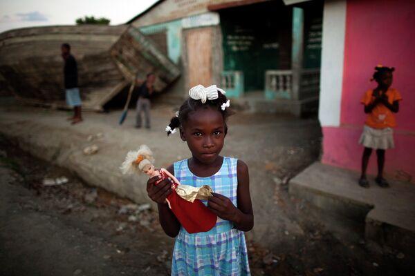 Девочка держит куклу Барби в Пор-де-Пе, Гаити