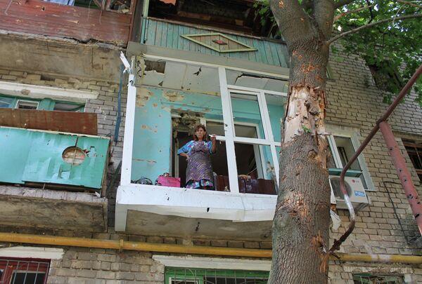 Женщина на балконе квартиры в Горловке после обстрела