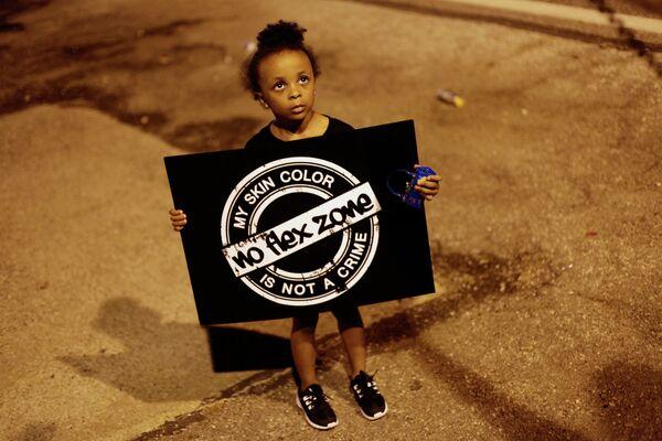 Девочка с плакатом во время протестов в городе Фергюсон, США
