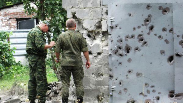 Сотрудники МЧС у ворот, поврежденных осколками в результате обстрела Донецка. Архивное фото