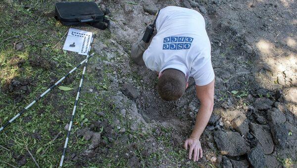 Сотрудники миссии ОБСЕ изучают воронку от разорвавшегося снаряда на территории школы № 16. Архивное фото